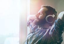 Pria duduk di sebelah jendela sambil memakai headphone (© Shutterstock)