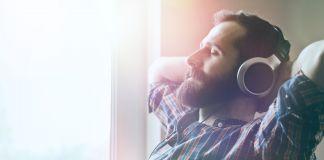 Un homme portant des écouteurs et assis dans un fauteuil près d'une fenêtre (© Shutterstock)