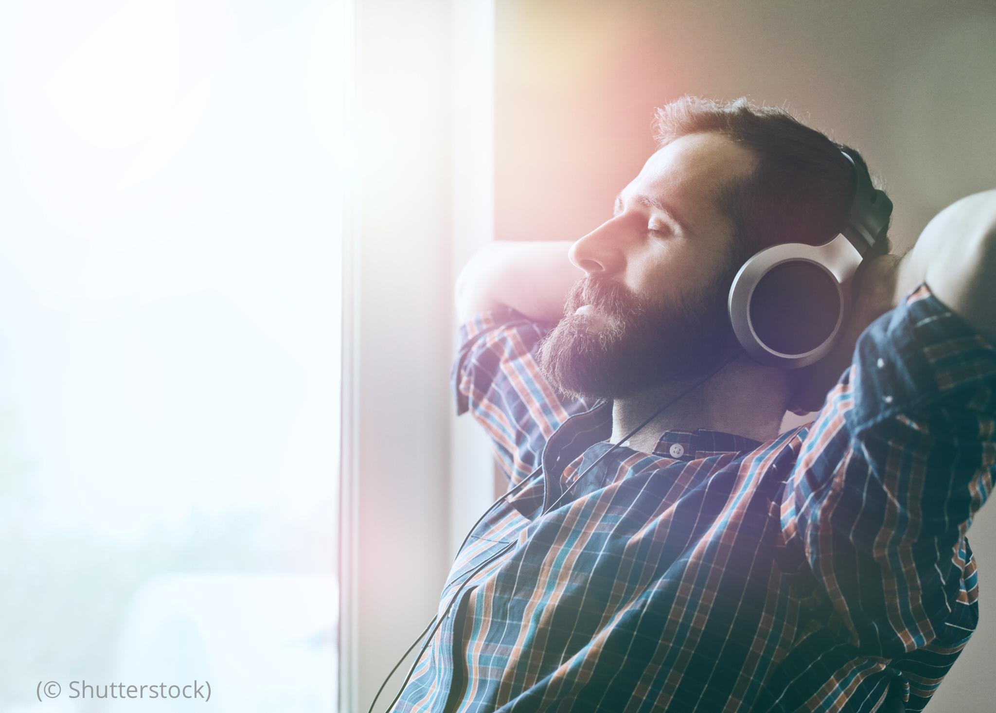 کانوں پر ہیڈفون لگائے کھڑکی کے قریب بیٹھا ایک آدمی۔ (© Shutterstock)