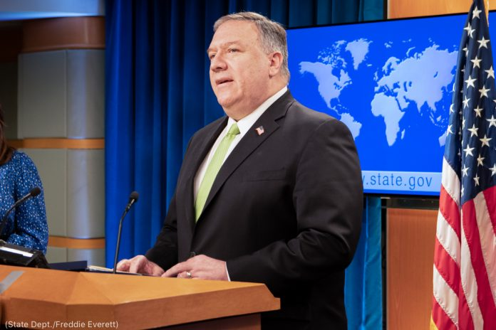 Pompeo standing and speaking next to U.S. flag with a world map on a screen behind him (State Dept./Freddie Everett)