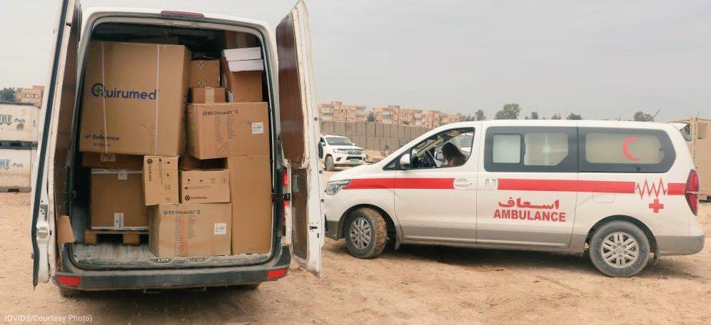 قریب ہی کھڑی ایمبولینس کے پاس ایک وین جس میں ڈبے پڑے ہوئے ہیں اور اس کا پچھلا دروازہ کھلا ہے۔ (DVIDS/Courtesy Photo)