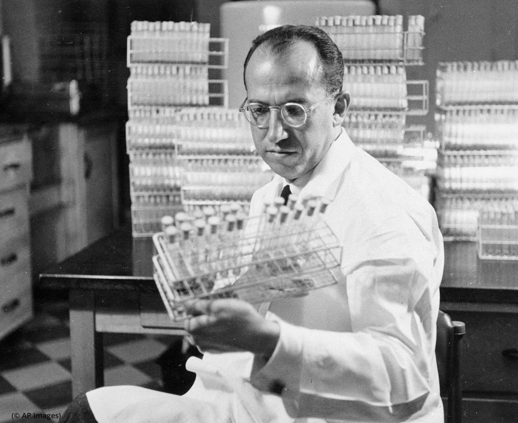 Dr. Jonas Salk looking at test tubes (© AP Images)