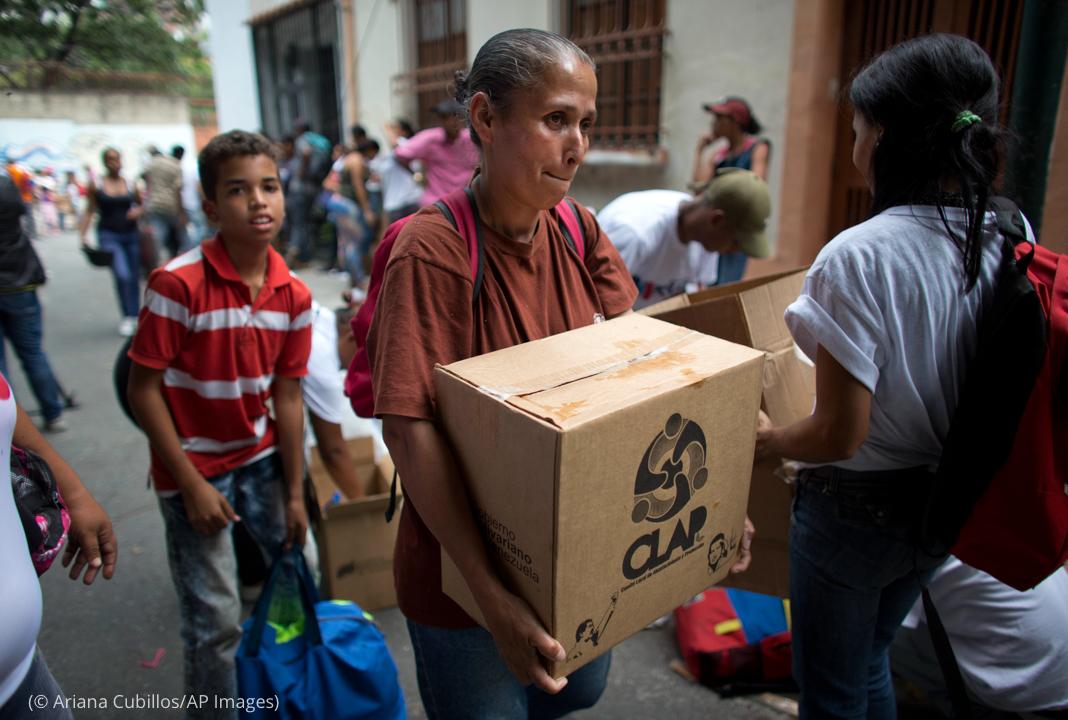 Woman carrying box (© Ariana Cubillos/AP Images)