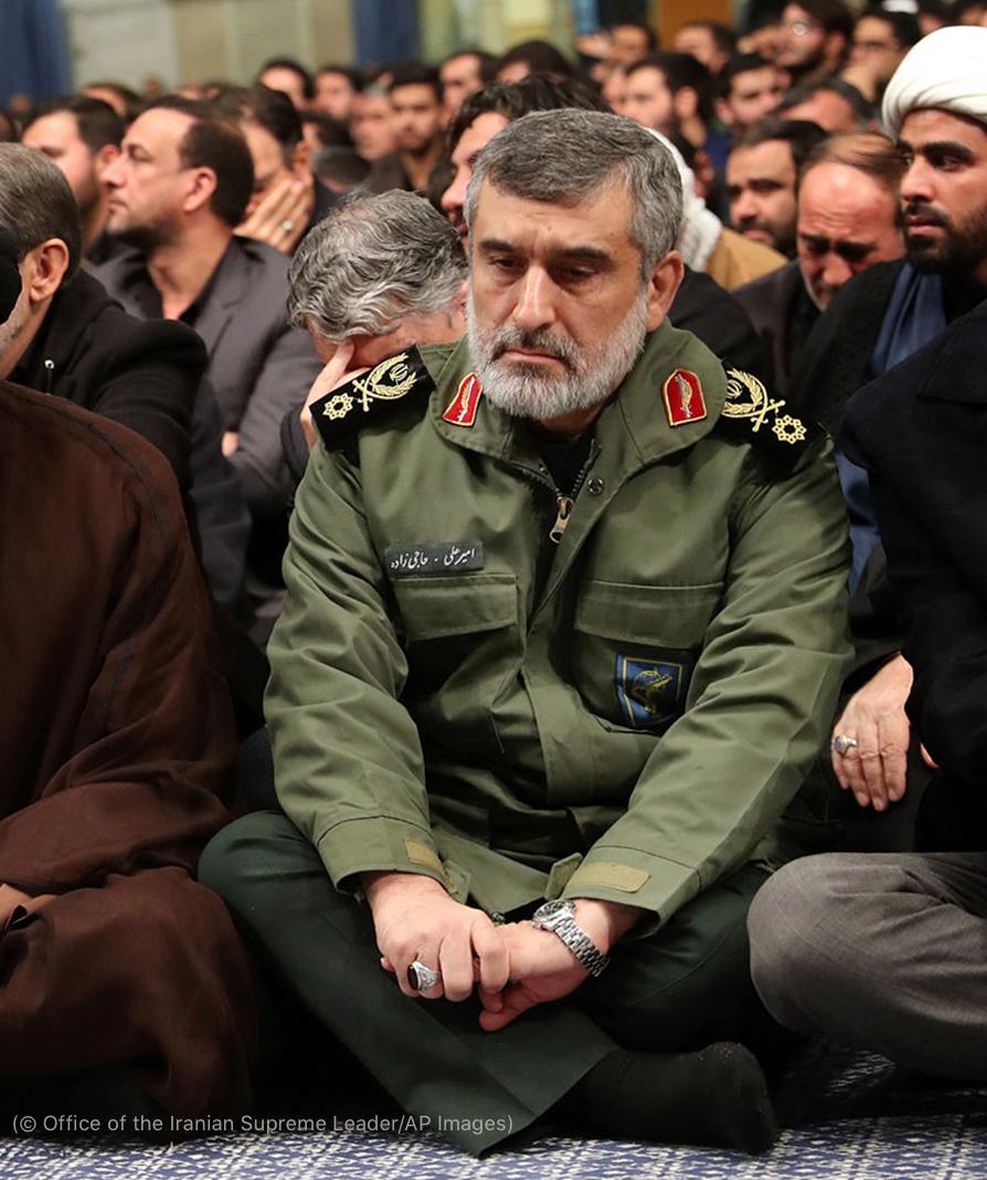 فوجی وردی میں ملبوس دیگر افراد کے ہمراہ فرش پر بیٹھا ہوا ایک فوجی افسر (© Office of the Iranian Supreme Leader/AP Images)