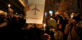 People holding candles and sign with airplane at night (© Ebrahim Noroozi/AP Images)