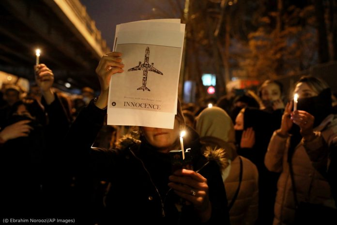 People holding a sign with an airplane and candles at night on a street (© Ebrahim Noroozi/AP Images)