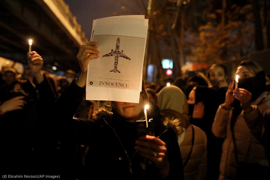 رات کے وقت لوگ موم بتیاں اور جہاز کی تصویر لیے کھڑے ہیں۔ (© Ebrahim Noroozi/AP Images)