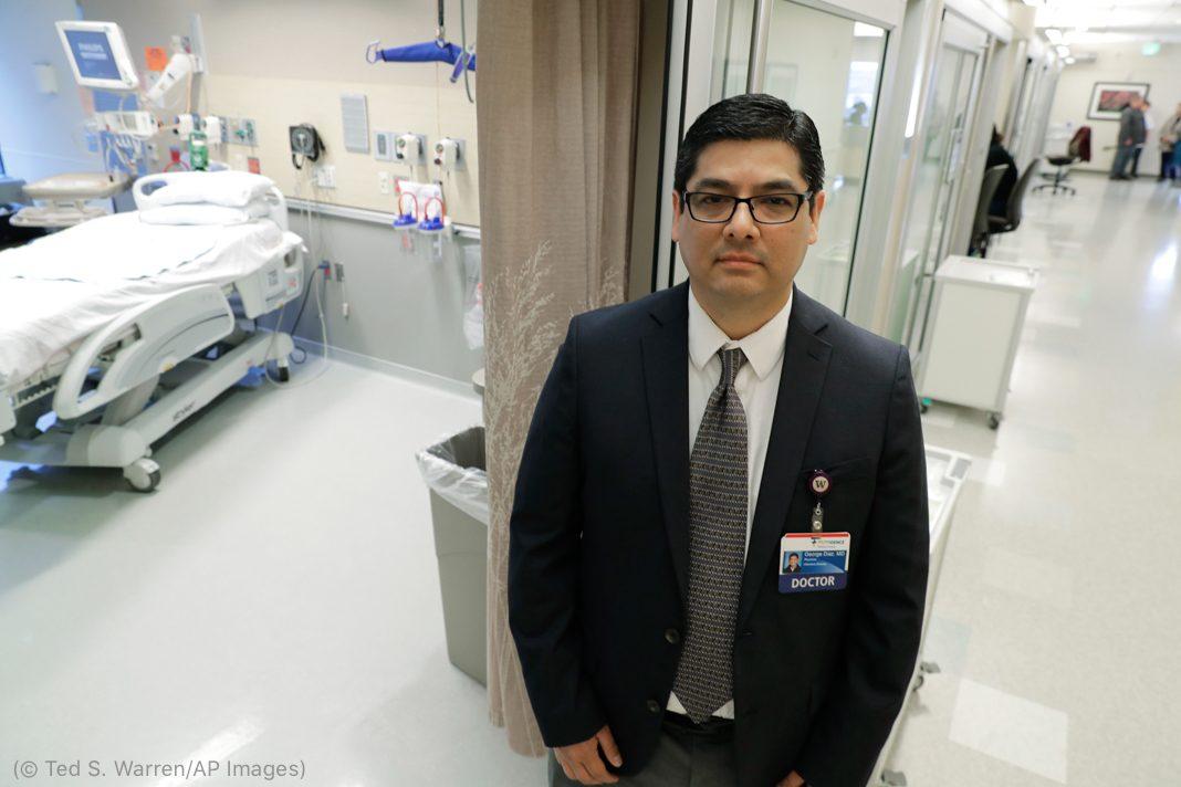 Hombre con traje en el pasillo de un hospital (© Ted S. Warren/AP Images)