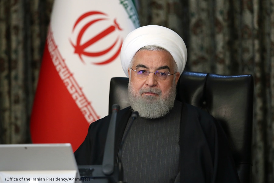 Hassan Rouhani sitting in front of flag (Office of the Iranian Presidency/AP Images)