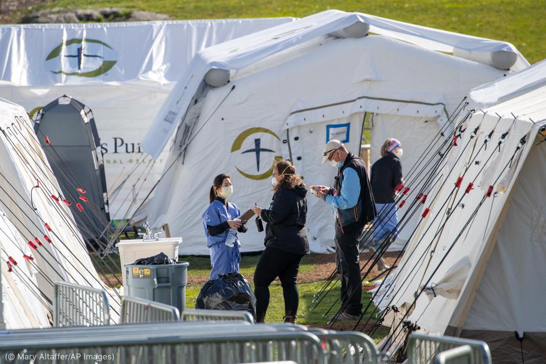 (© Mary Altaffer/AP Images)خیموں کے درمیان کھڑے لوگ۔ (© Mary Altaffer/AP Images)