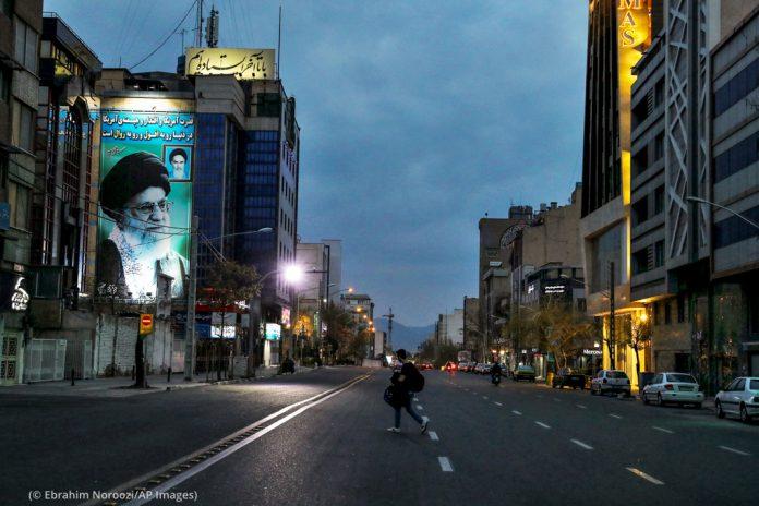Personal walking down dark and empty street (© Ebrahim Noroozi/AP Images)