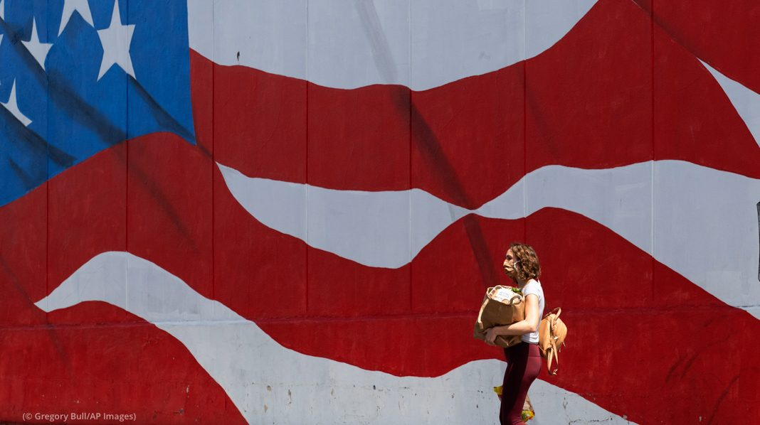 Une femme portant des sacs de provisions et passant devant un gigantesque drapeau américain peint sur un mur (© Gregory Bull/AP Images)