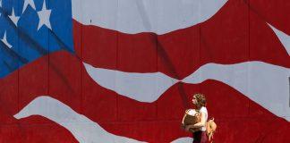 Wanita membawa barang belanjaan berjalan melewati mural bendera AS (© Gregory Bull/AP Images)