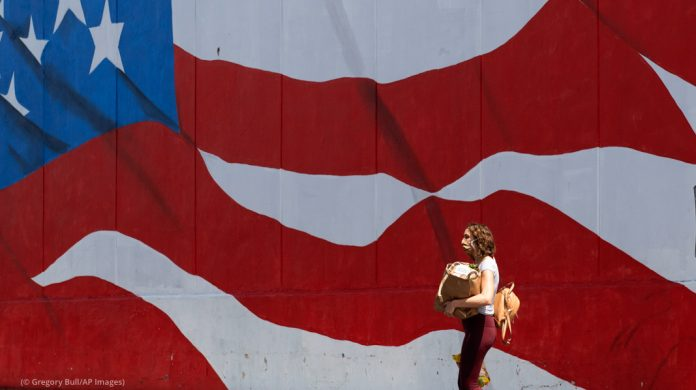 Woman with groceries walking past an American flag mural (© Gregory Bull/AP Images)