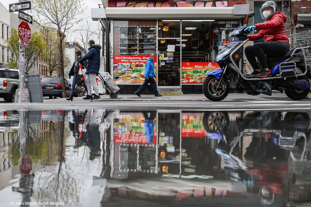 Person riding motorbike and people waling past grocery store, with their reflection in pooled water on street (© John Minchillo/AP Images)
