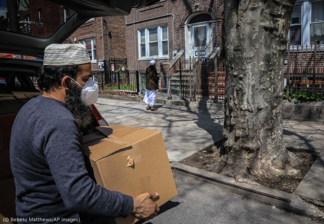 Two men carrying boxes in residential area (© Bebeto Matthews/AP Images)