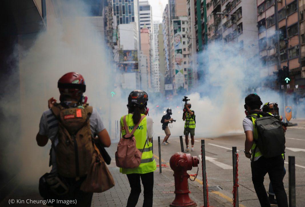 Personas corren para ponerse a cubierto de gases lacrimógenos (© Kin Cheung/AP Images)