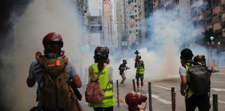 Pessoas correm para se proteger de gás lacrimogêneo (© Kin Cheung/AP Images)