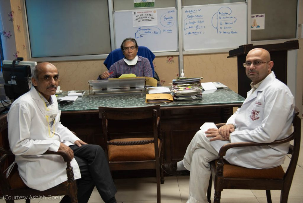 Three men sitting in an office (Courtesy of Ashish Goel)