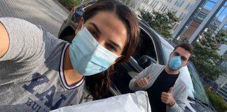 Seorang perempuan bermasker memegang paket dengan pria di belakangnya yang sedang mengacungkan jempol (© COVIDsitters)
