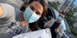 Woman in a face mask holding a package with man behind her with thumbs up (© CovidSitters)