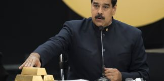 Nicolás Maduro touching stack of gold bars (© Carlos Becerra/Bloomberg/Getty Images)