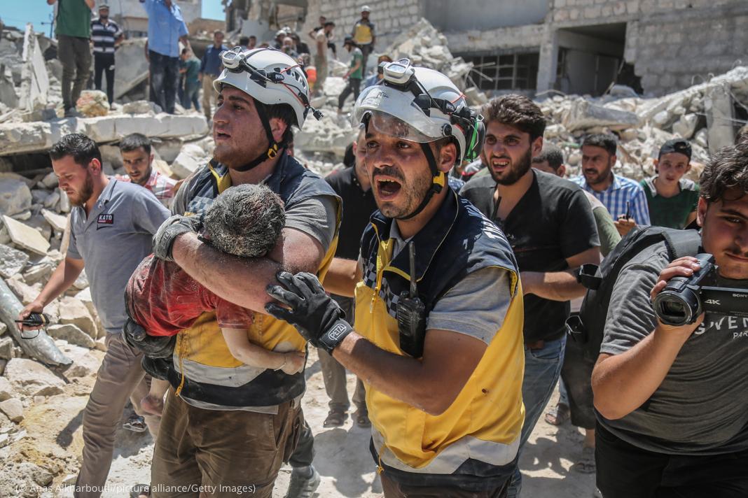 Hombre sacando de los escombros a un niño herido (© Anas Alkharboutli/picture alliance/Getty Images)