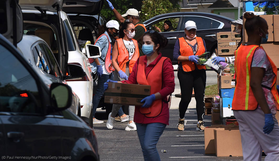People wearing masks carrying boxes to and from cars (© Paul Hennessy/NurPhoto/Getty Images)