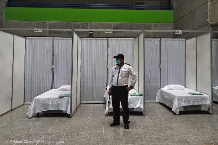 Guard wearing face mask standing in front of beds separated by partitions (© Orlando Sierra/AFP/Getty Images)