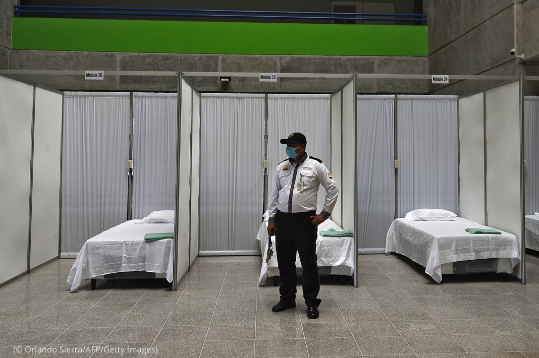 A guard wearing a face mask standing in front of beds in a makeshift hospital in Hon