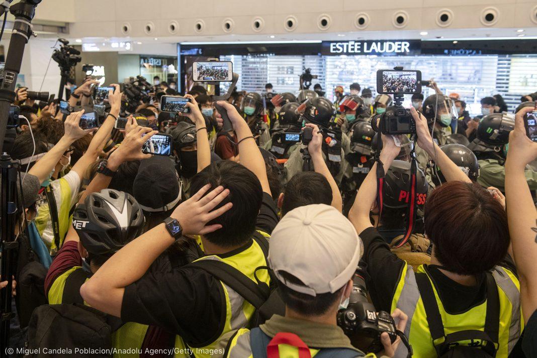 Des gens en train de photographier et de filmer des policiers dans un centre commercial (© Miguel Candela Poblacion/Anadolu Agency/Getty Images)