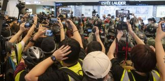 Journalists photographing and filming police officers in a mall (© Miguel Candela Poblacion/Anadolu Agency/Getty Images)