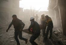 Men carrying person on stretcher through smoke and rubble (© Amer Almohibany/AFP/Getty Images)