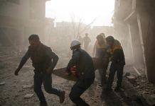 在烟雾和残垣中,几名男子抬着一个躺在担架上的人(© Amer Almohibany/AFP/Getty Images)