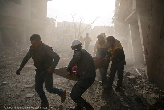 Homens carregando uma pessoa em maca através de fumaça e escombros (© Amer Almohibany/AFP/Getty Images)