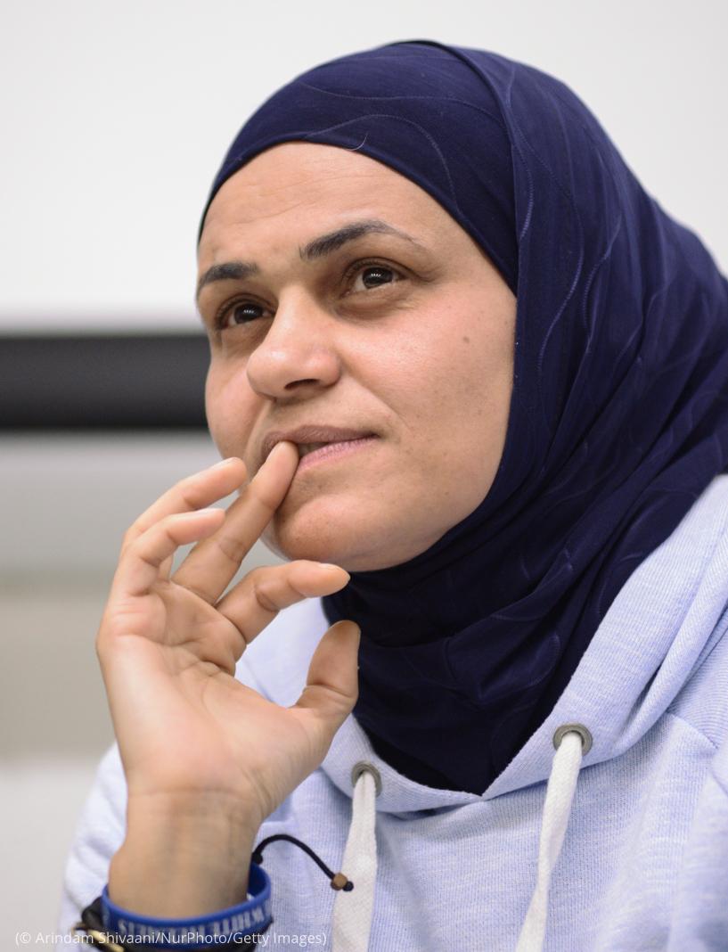 Mujer con la mano en la boca mientras escucha (© Arindam Shivaani/NurPhoto/Getty Images)