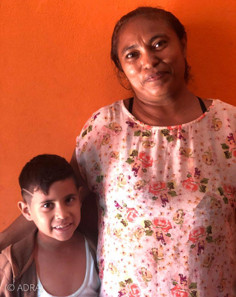 Mãe de pé com o filho (© Adra)
