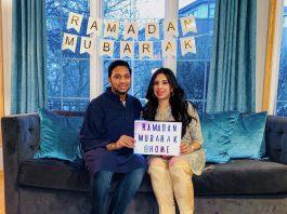 Homem e mulher sentados em um sofá de uma sala com decorações do Ramadã (Cortesia: Salman Azam)