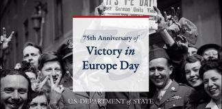 People surrounding sign saying 'Victory in Europe Day' (State Dept.)