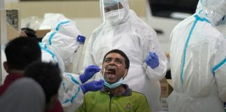 People in protective gear surrounding man with open mouth (State Dept.)