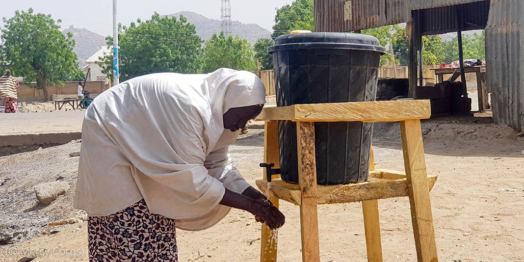 Woman bending over to wash hands from water dispenser (© Mercy Corps)