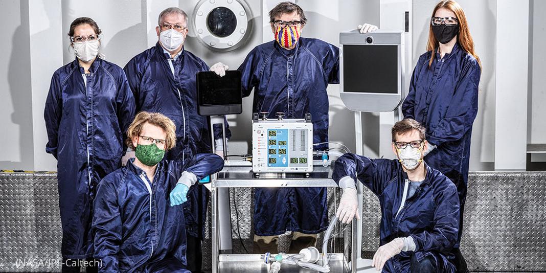 حفاظتی لباس پہنے لوگ وینٹی لیٹر کے نمونے کے پاس کھڑے ہیں (NASA/JPL-Caltech)