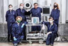 Six personnes portant des équipements de protection posant autour d'un prototype de respirateur (NASA/JPL-Caltech)