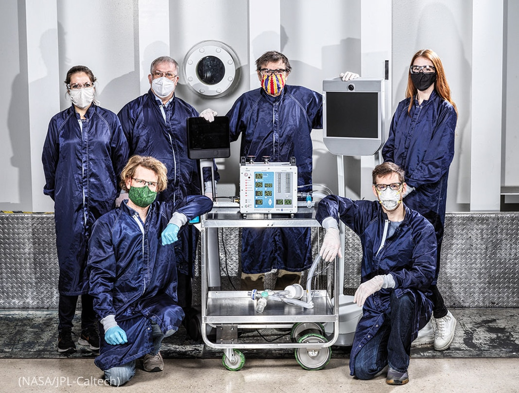 People in protective gear posing with a ventilator prototype (NASA/JPL-Caltech)