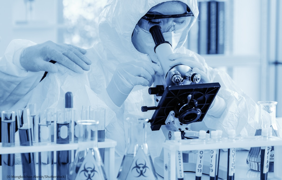 Persona con traje protector mira por un microscopio (© Mongkolchon Akesin/Shutterstock)