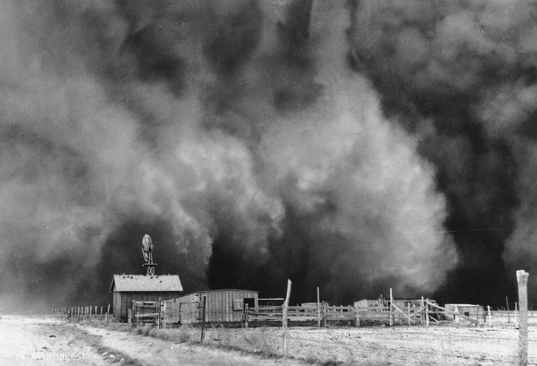 Historic photo of a dust cloud approaching a ranch (© AP Images)