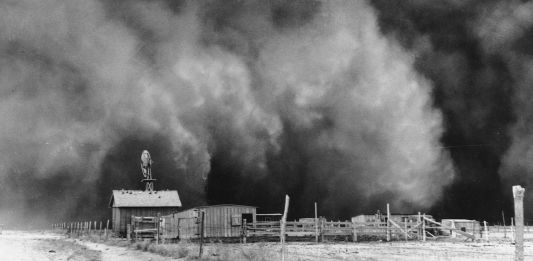Historic photo of dust cloud approaching buildings (© AP Images)