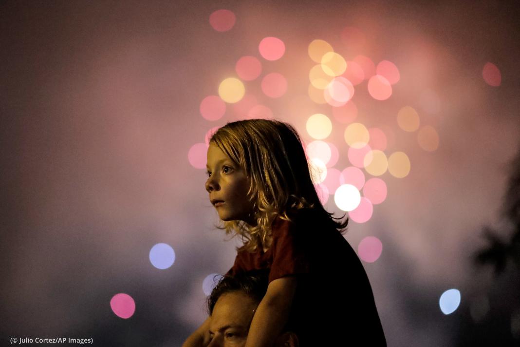Anak kecil duduk di bahu orang dewasa menonton kembang api (© Julio Cortez/AP Images)