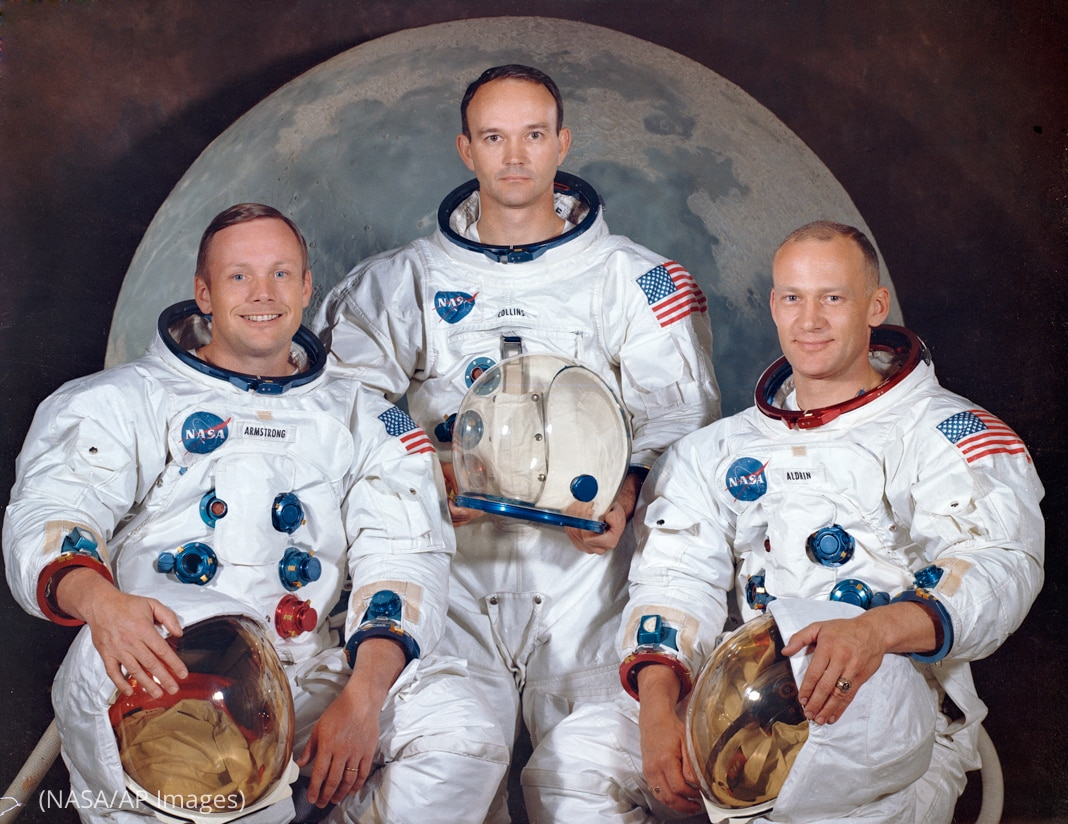 Three men in spacesuits posing in front of image of moon (NASA/AP Images)