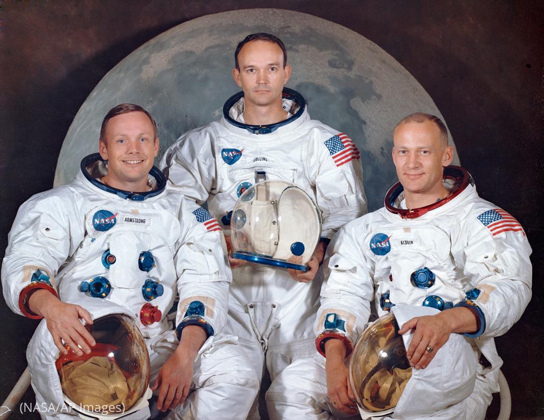 Tres hombres en traje espacial posan al frente de una imagen de la Luna (NASA/AP Images)